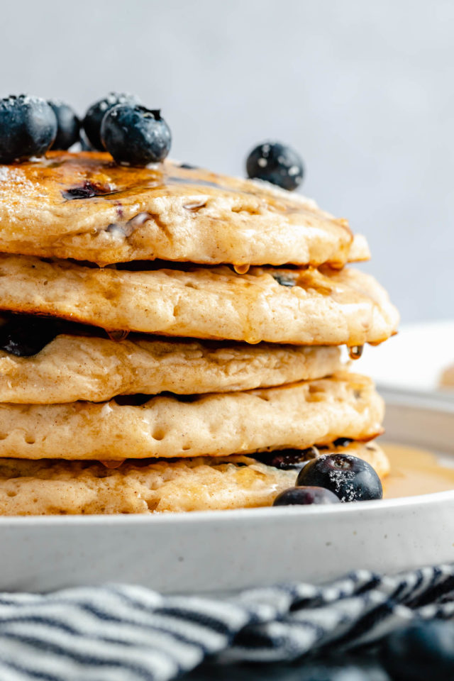 stack of pancakes topped with fresh blueberries