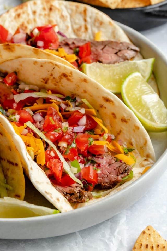 carne asada tacos on a plate with a lime wedge