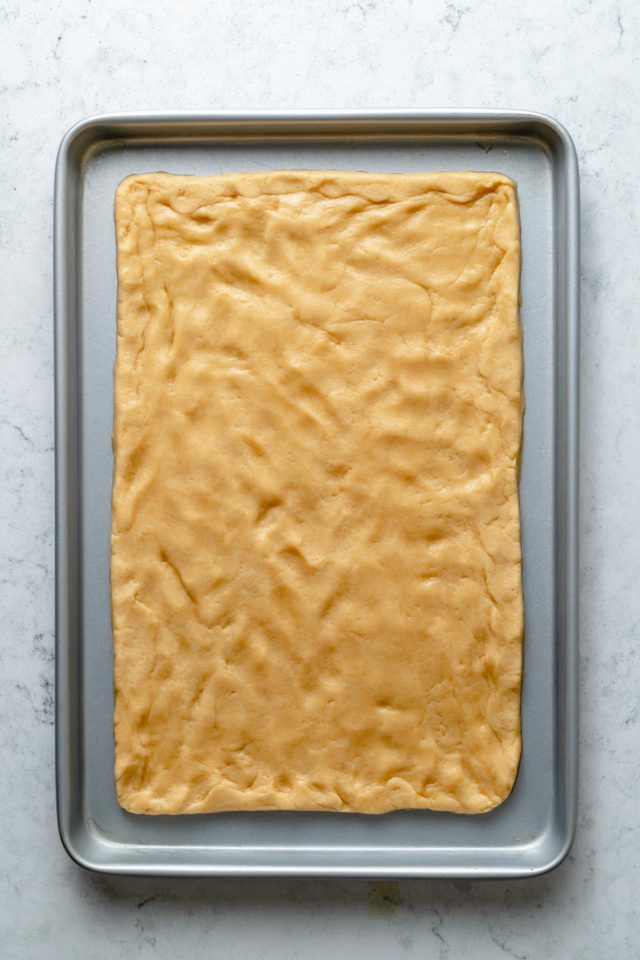 spreading sugar cookie dough out over a cookie sheet