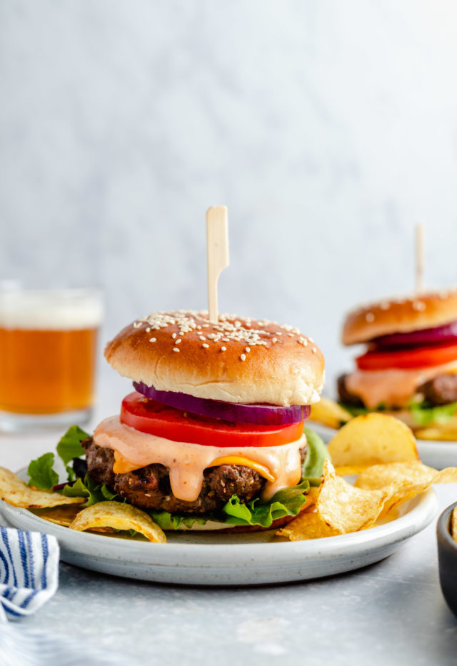 burgers served on a plate with potato chips and a beer