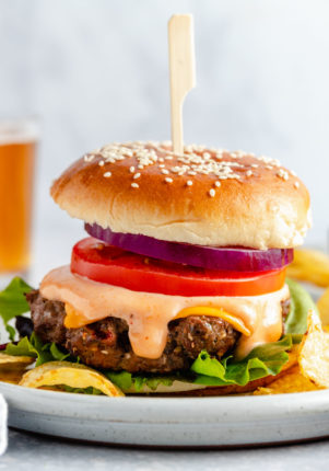 healthy burgers topped with cheese, burger sauce, tomato and red onion