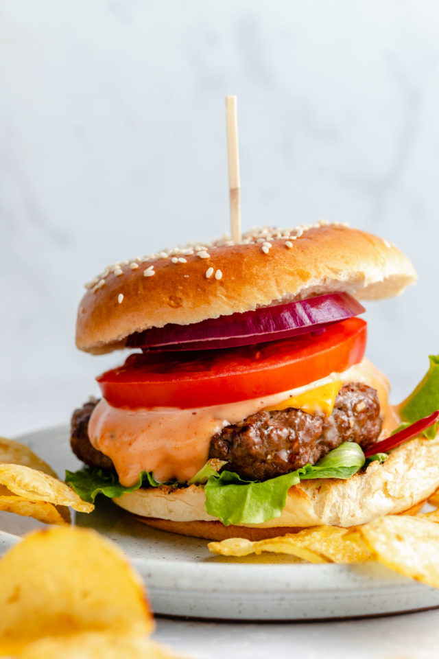 cheeseburger with all of the fixings on a plate with chips