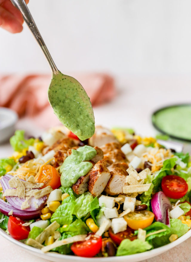drizzling southwest salad dressing over a salad topped with chicken