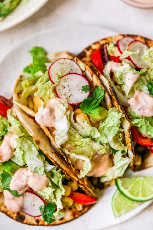 vegetarian tacos served on a plate and topped with cabbage slaw, radishes and chipotle sauce
