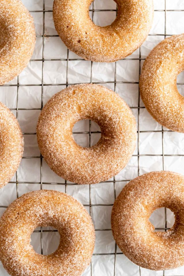 apple cider donuts covered in cinnamon/sugar on a wire cooling rack