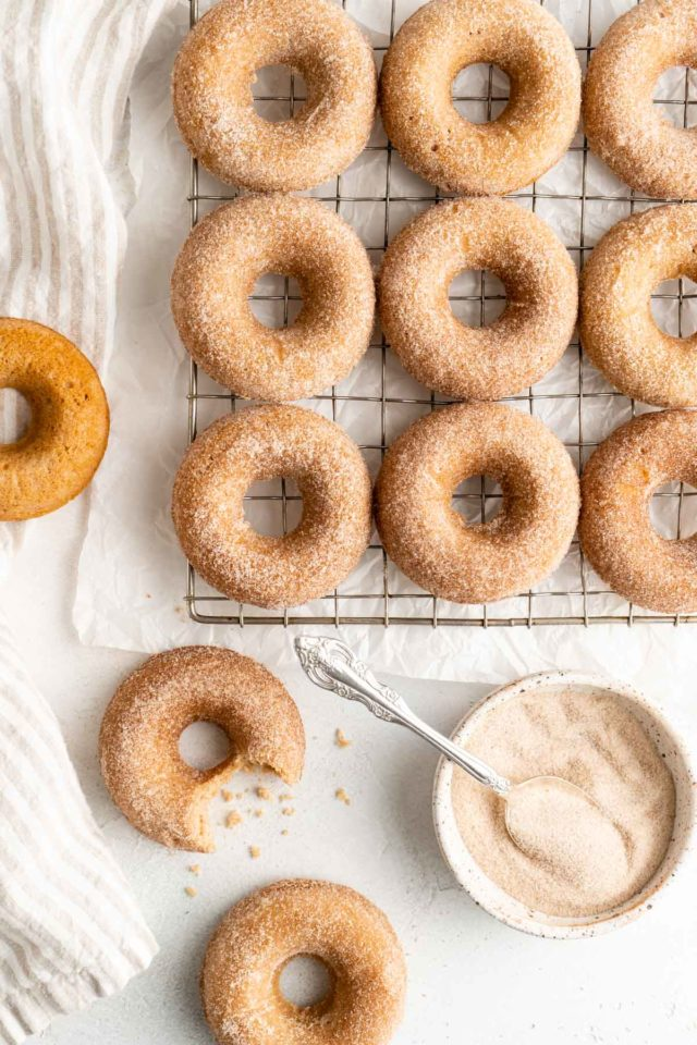 apple cider donuts with cinnamon sugar coating on a wire cooling rack