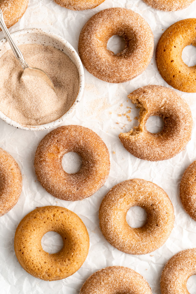 covering apple cider donuts with cinnamon sugar coating