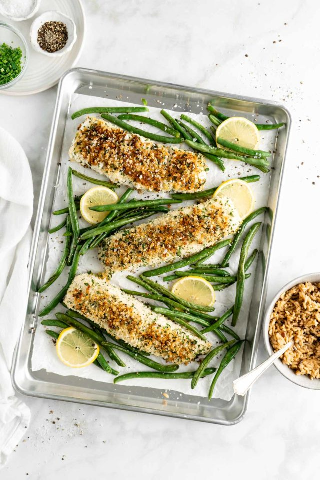 baked halibut on a baking sheet with green beans and lemon wedges