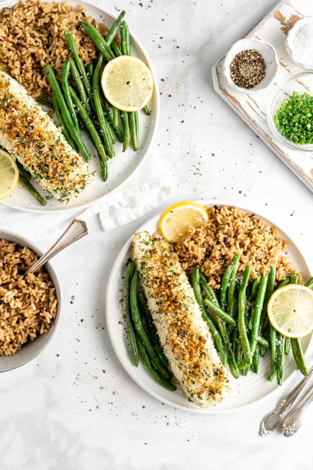 baked halibut served on white plates with roasted green beans and slices of lemon