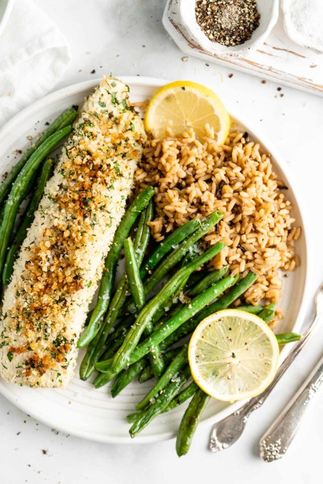 baked halibut plated with roasted green beans and rice