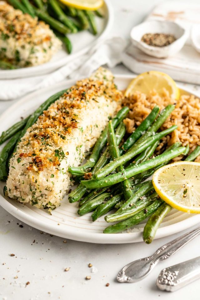 panko crusted halibut served with green beans, rice and slices of lemon