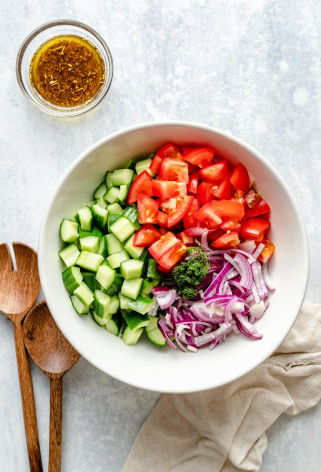 chopped tomato, cucumber and red onion in a large white bowl