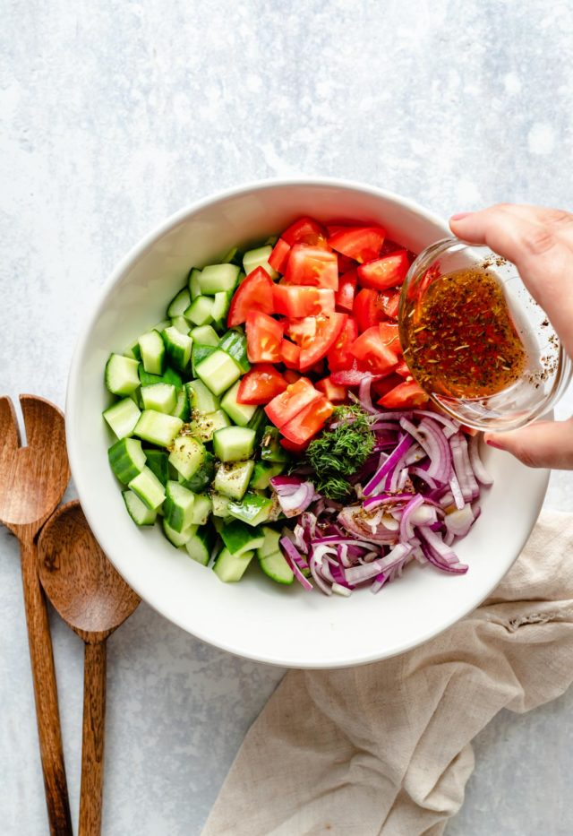 pouring dressing over cucumber tomato salad