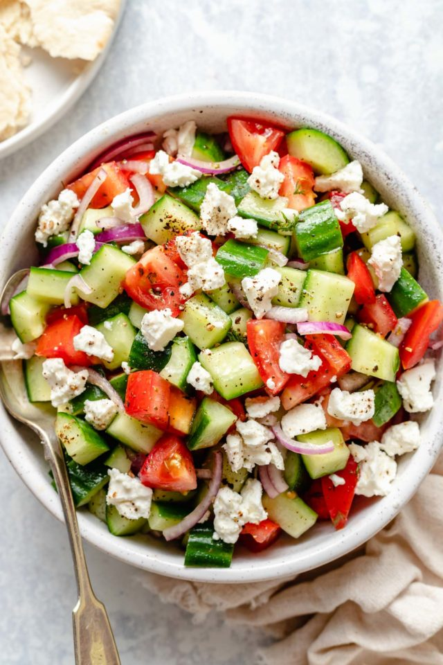 cucumber tomato salad served with a serving spoon