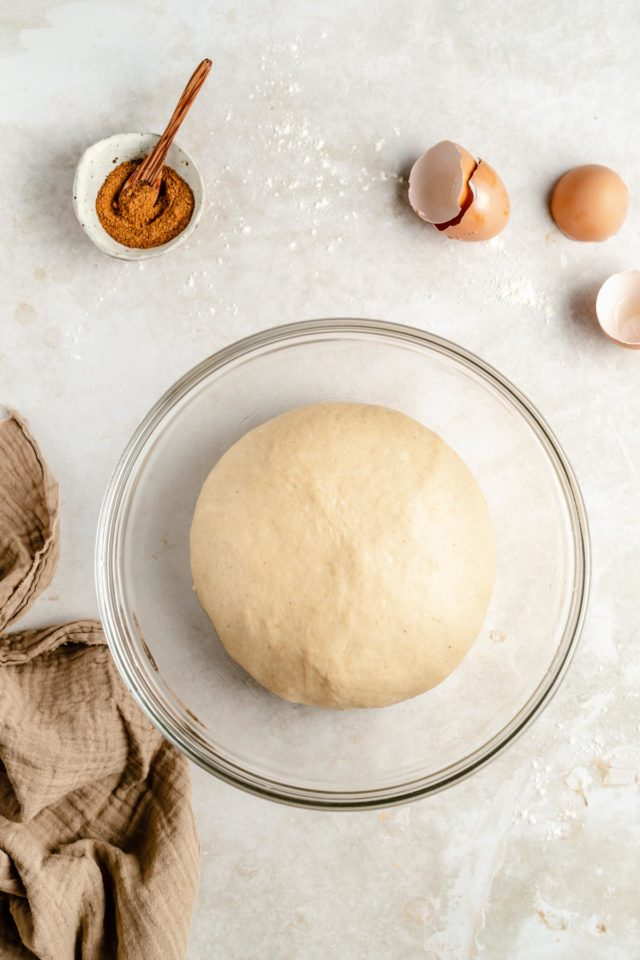 round ball of dough in a glass mixing bowl