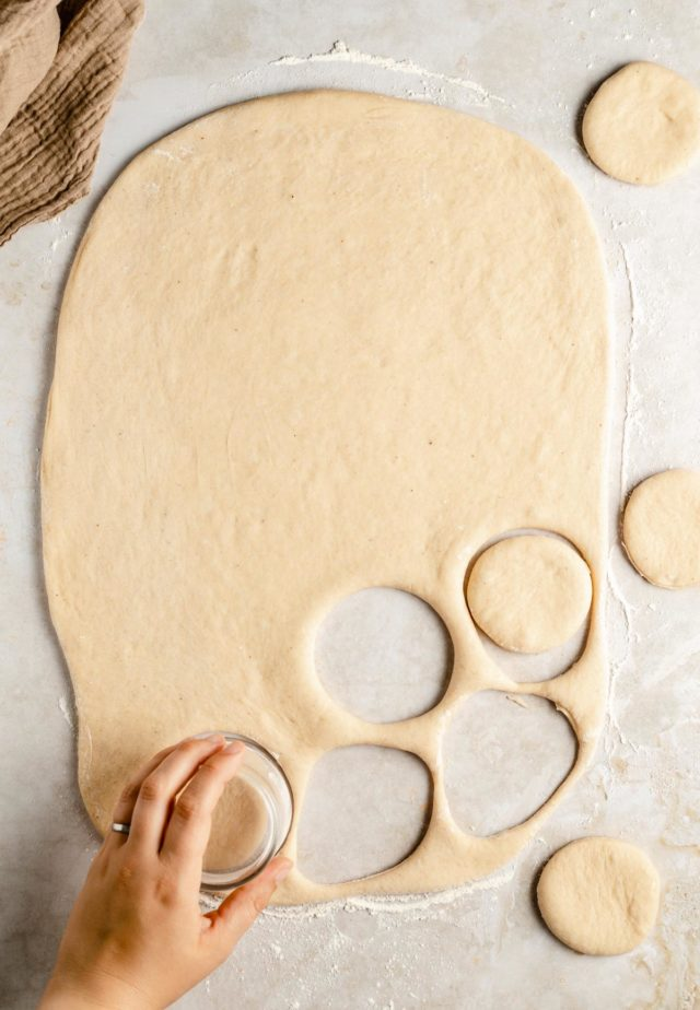 cutting round circles of dough to make donuts