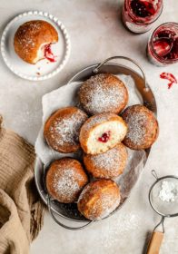 jelly donuts dusted with powdered sugar on a serving tray