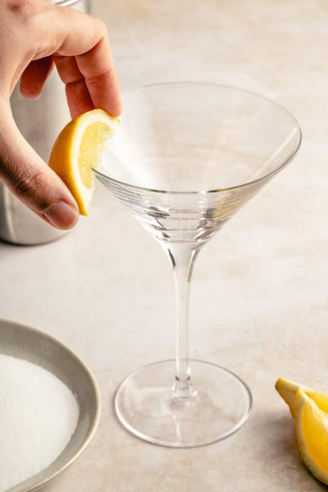 rubbing a lemon wedge along the edge of a martini glass