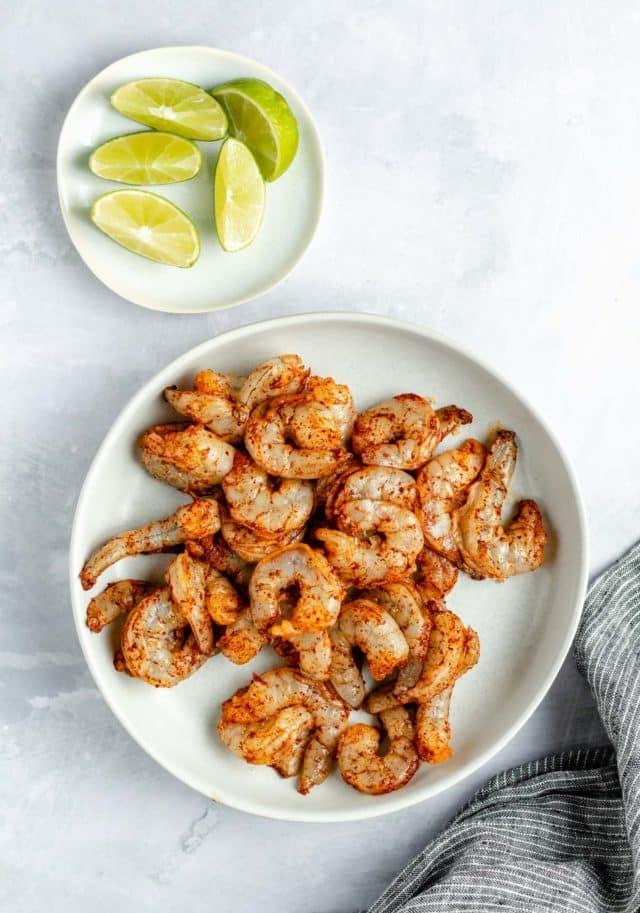 raw seasoned shrimp in a white bowl near fresh lime wedges