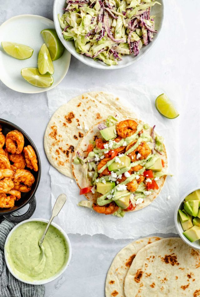 shrimp tacos served with avocado sauce and lime wedges