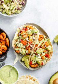 shrimp tacos topped with diced avocado