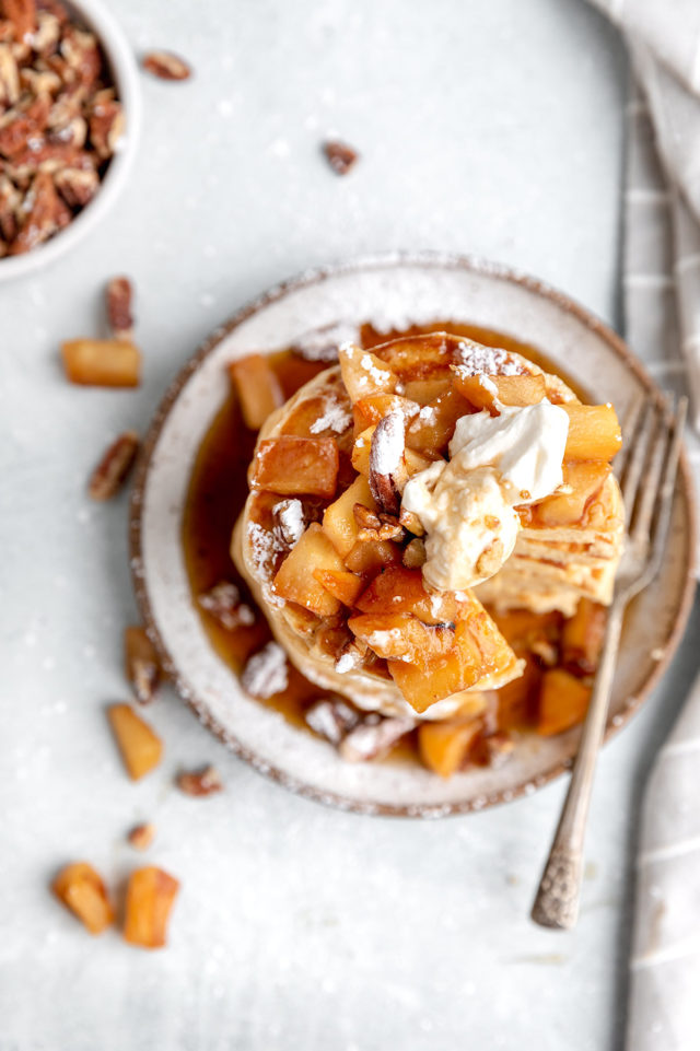 pancakes topped with diced apple, yogurt and pecans