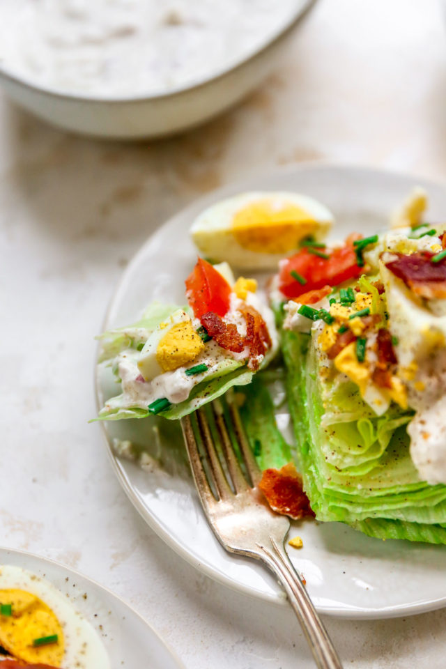 using a fork to take a bite of a wedge salad