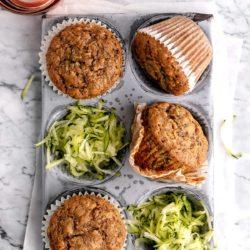 zucchini muffins in a muffin pan with shredded zucchini