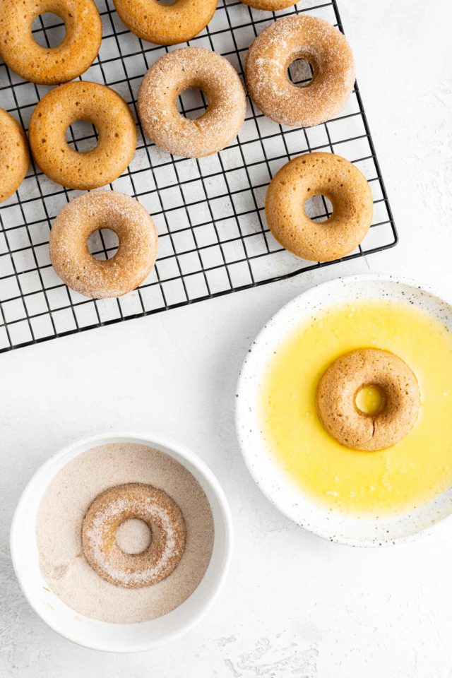 dipping donut in melted butter and then in cinnamon/sugar mix