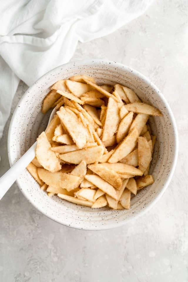 stirring apple slices with cinnamon and nutmeg