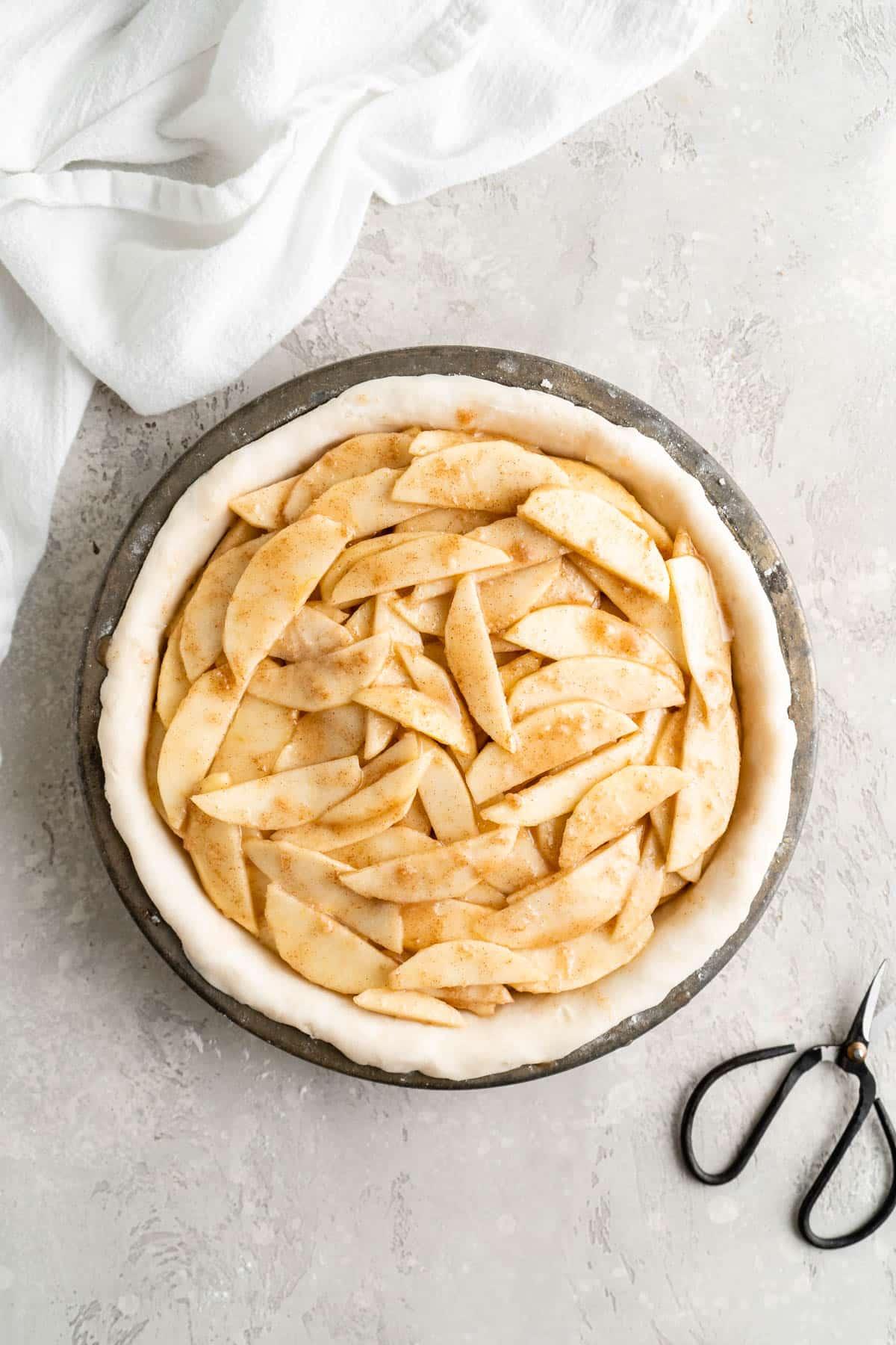 adding apple pie filling over bottom pie crust