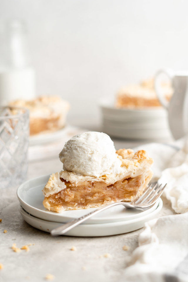 slice of apple pie topped with a scoop of ice cream, served on a white plate