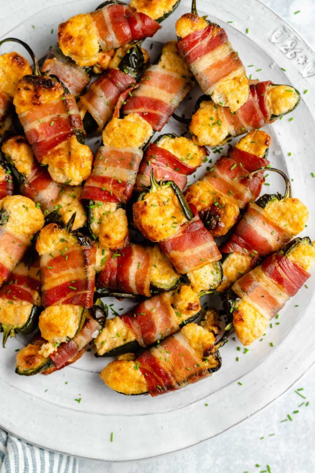 bacon wrapped jalapeno poppers on a large white serving tray
