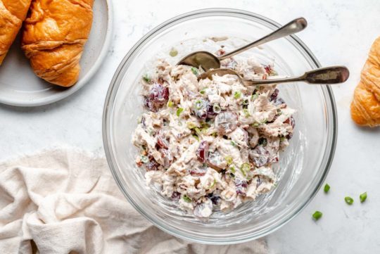 making chicken salad in a large glass mixing bowl