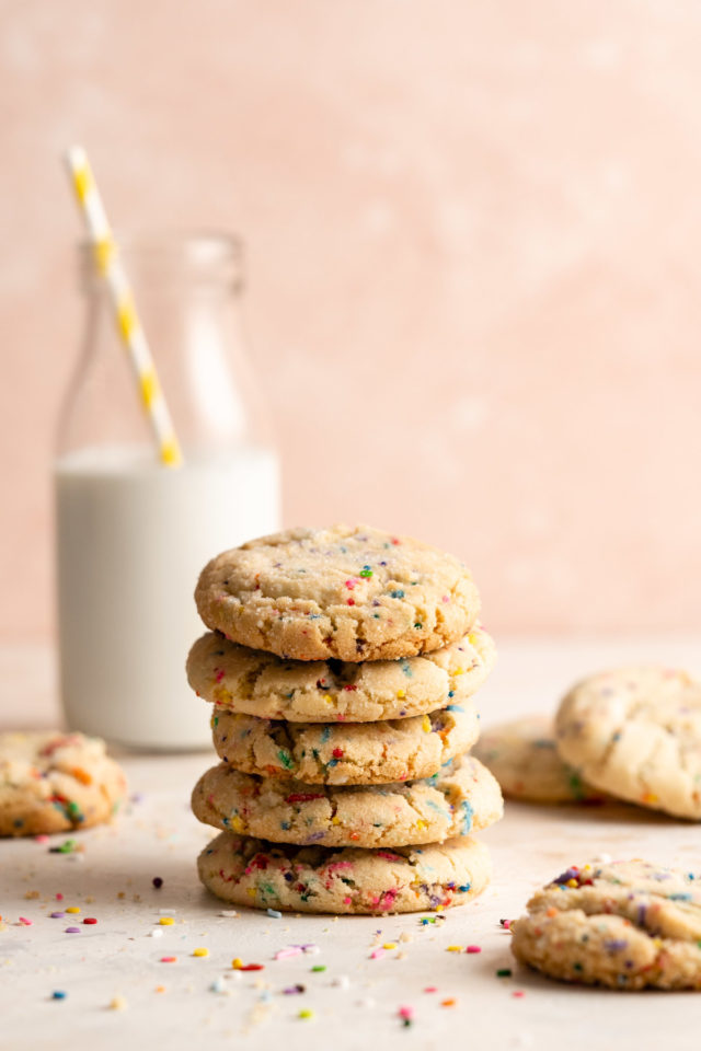 funfetti cookies stacked and served with milk