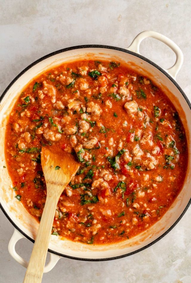 stirring ground sausage with tomatoes and fresh basil