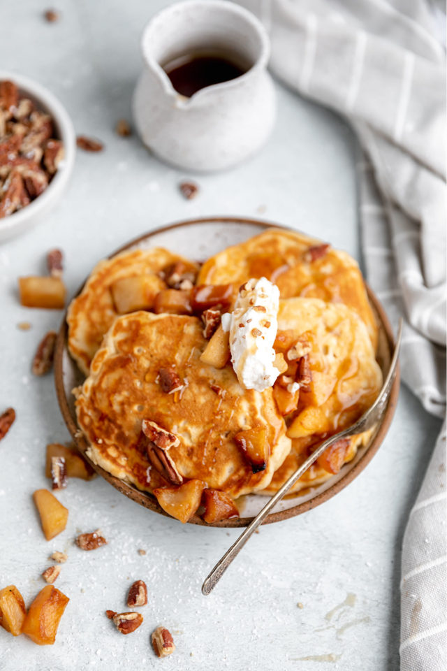 pancakes served with apples, chopped pecans and maple syrup