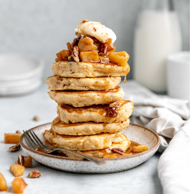 apple pancakes topped with apples, whipped cream and maple syrup
