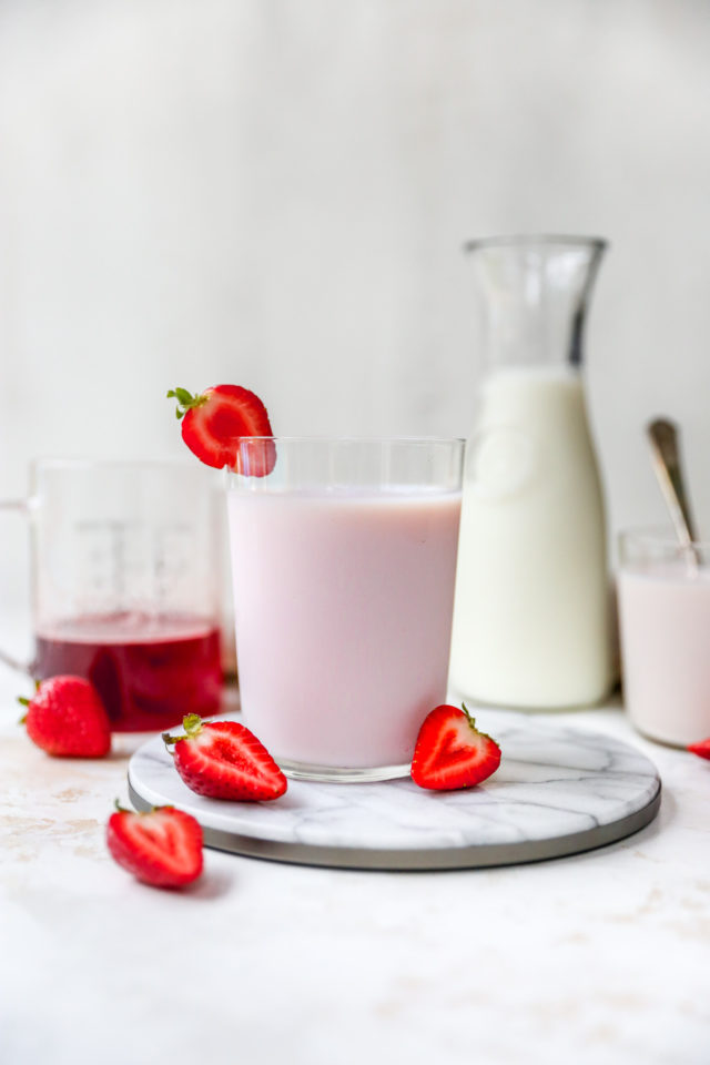 glass filled with strawberry milk near a carafe of milk