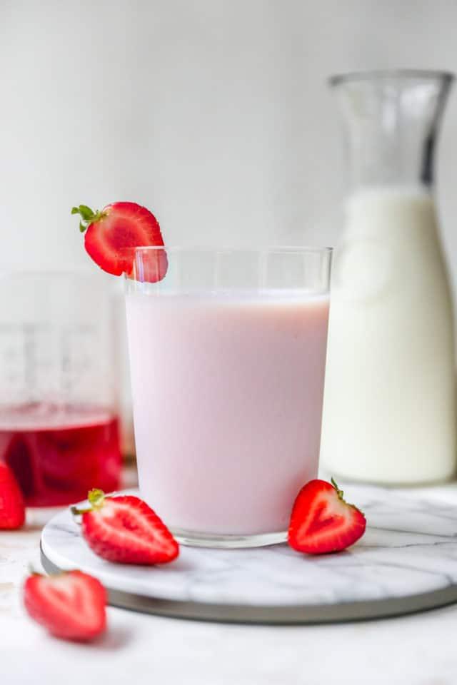 a glass of strawberry milk near fresh strawberries