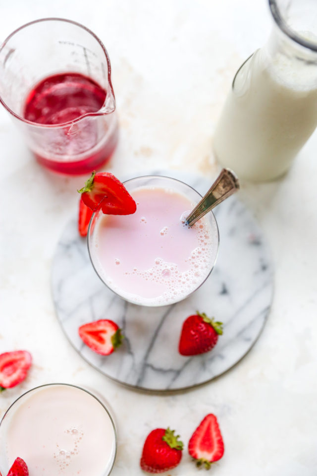 stirring strawberry syrup into milk