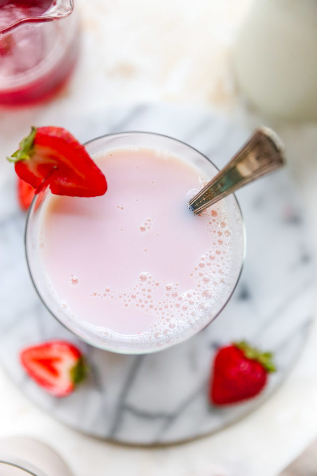 glass of strawberry milk garnished with a fresh strawberry