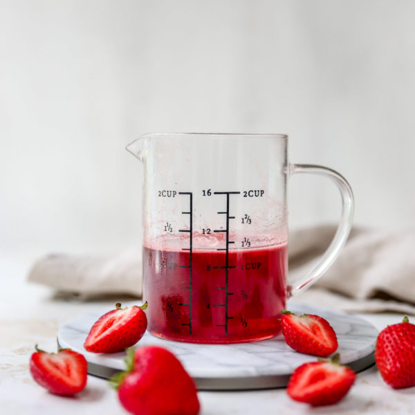 strawberry simple syrup in a measuring glass