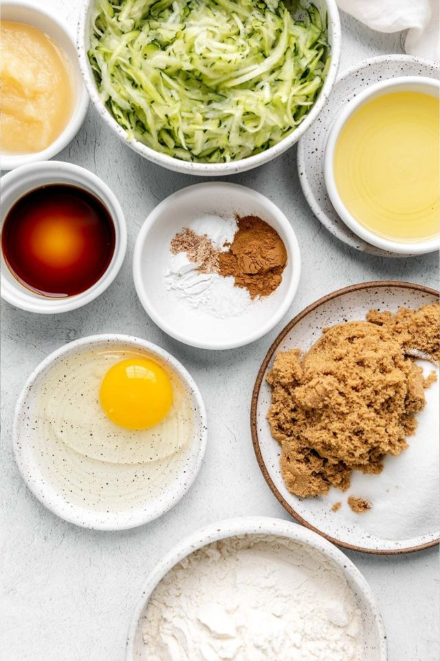 ingredients for making zucchini bread in small white bowls