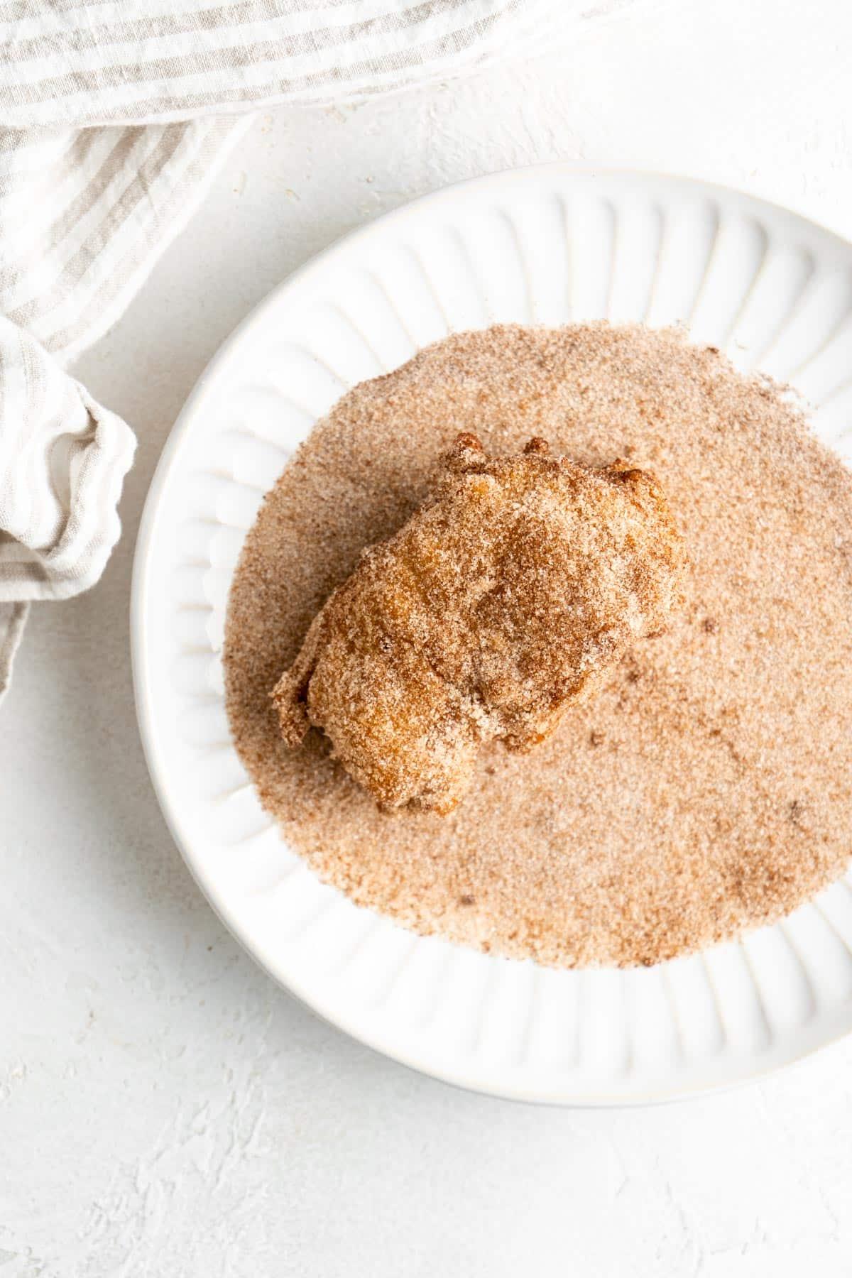 rolling apple fritters in cinnamon & sugar mixture