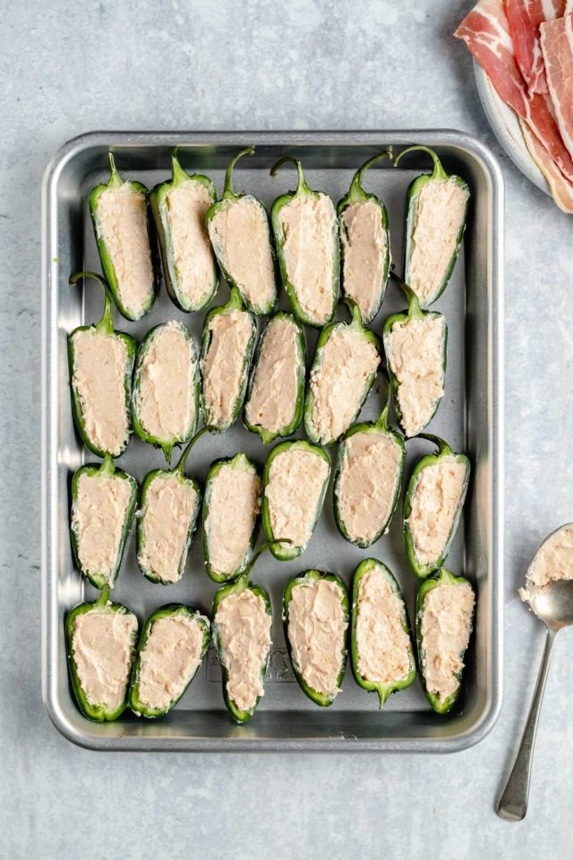 sliced jalapeño peppers stuffed with cream cheese mixture on a baking sheet