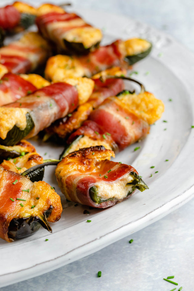 bacon-wrapped jalapeno poppers on a white serving plate