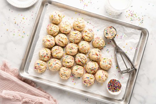 scoops of funfetti cookie dough on a baking sheet pan