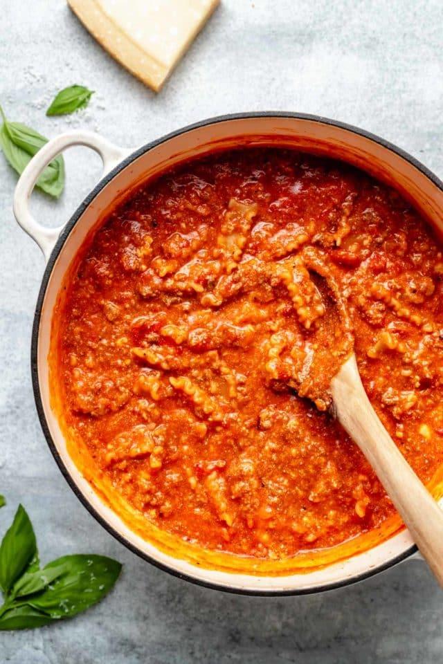 stirring noodles into a large pot of lasagna soup