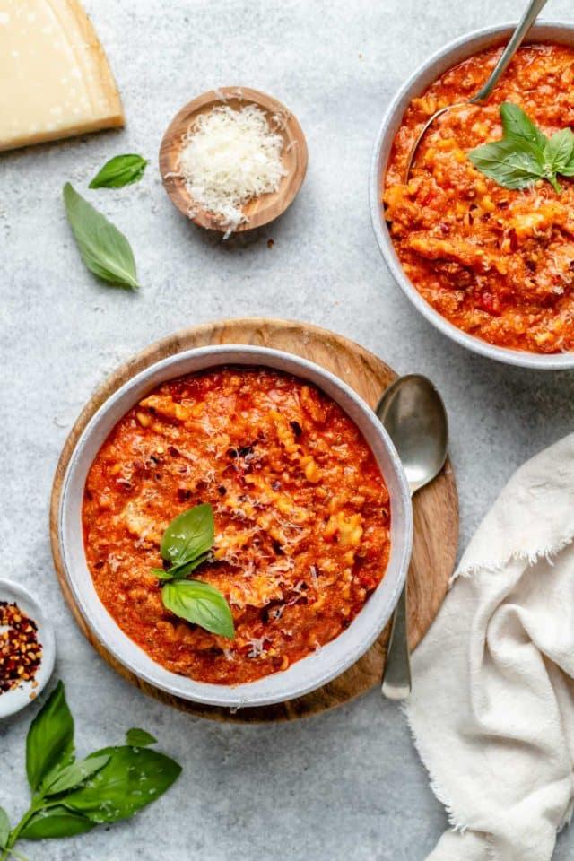 bowls of lasagna soup served with fresh basil and parmesan cheese